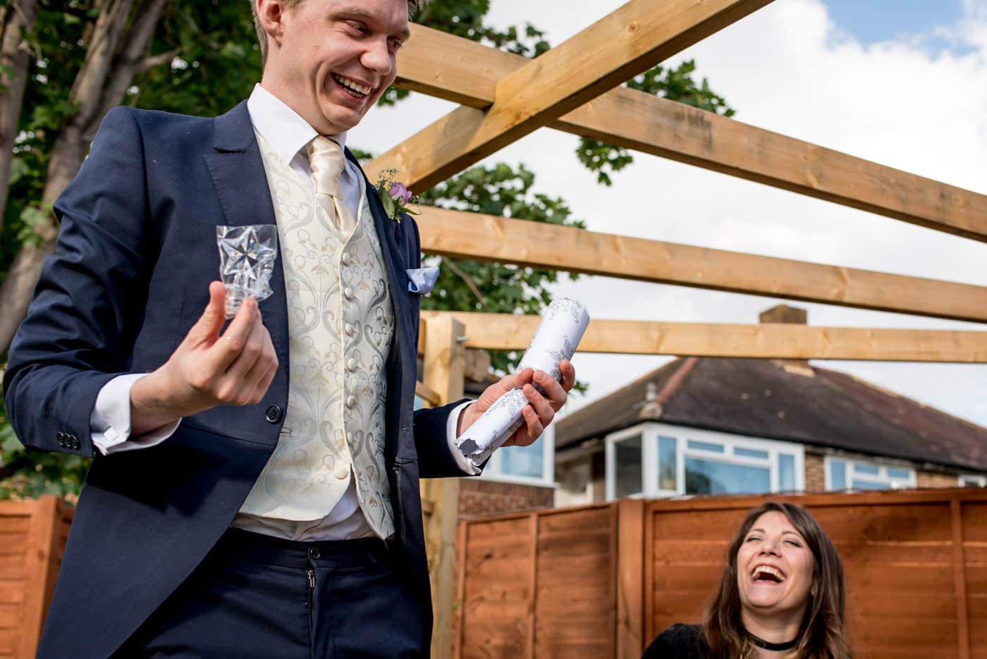 best man opening a party cracker at this intimate london wedding