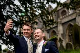 groom and bestman selfie in front of Carshalton church