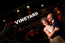 night portrait of bride and groom laughing in front of the vineyard in islington