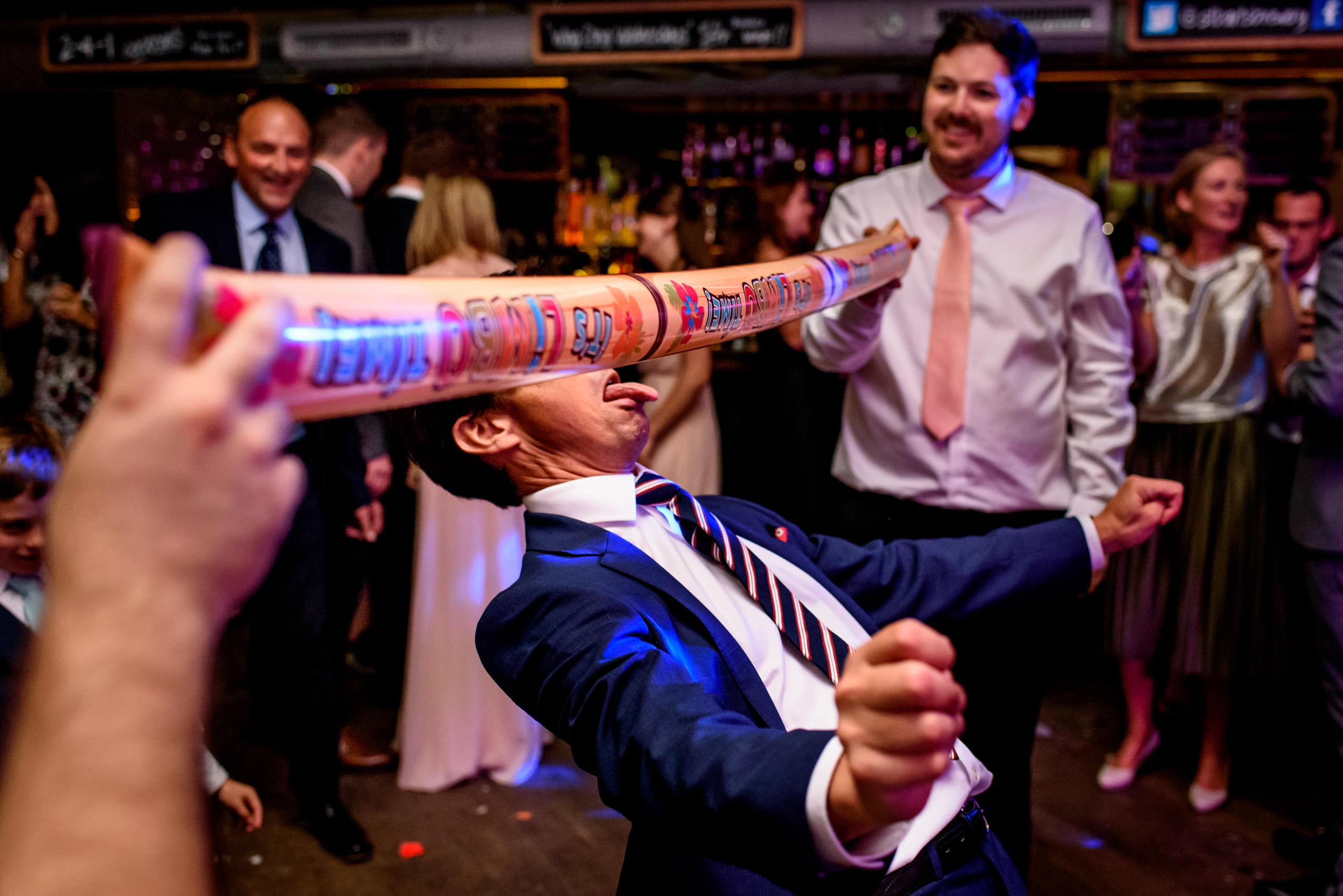 a wedding doing limbo under an inflatable limbo stick on the dance floor
