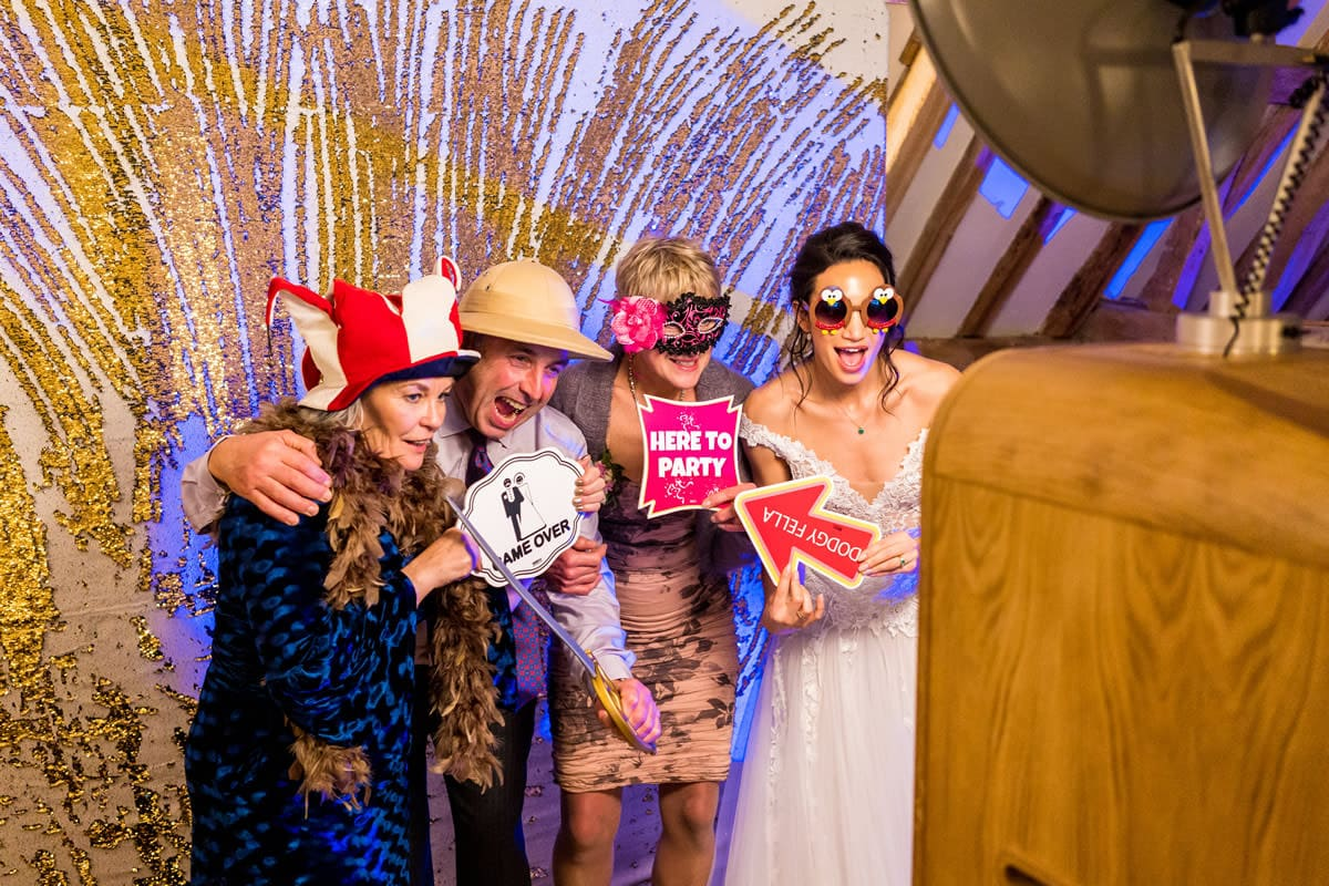 photo of wedding guests and the bride in fancy dress using a photo booth