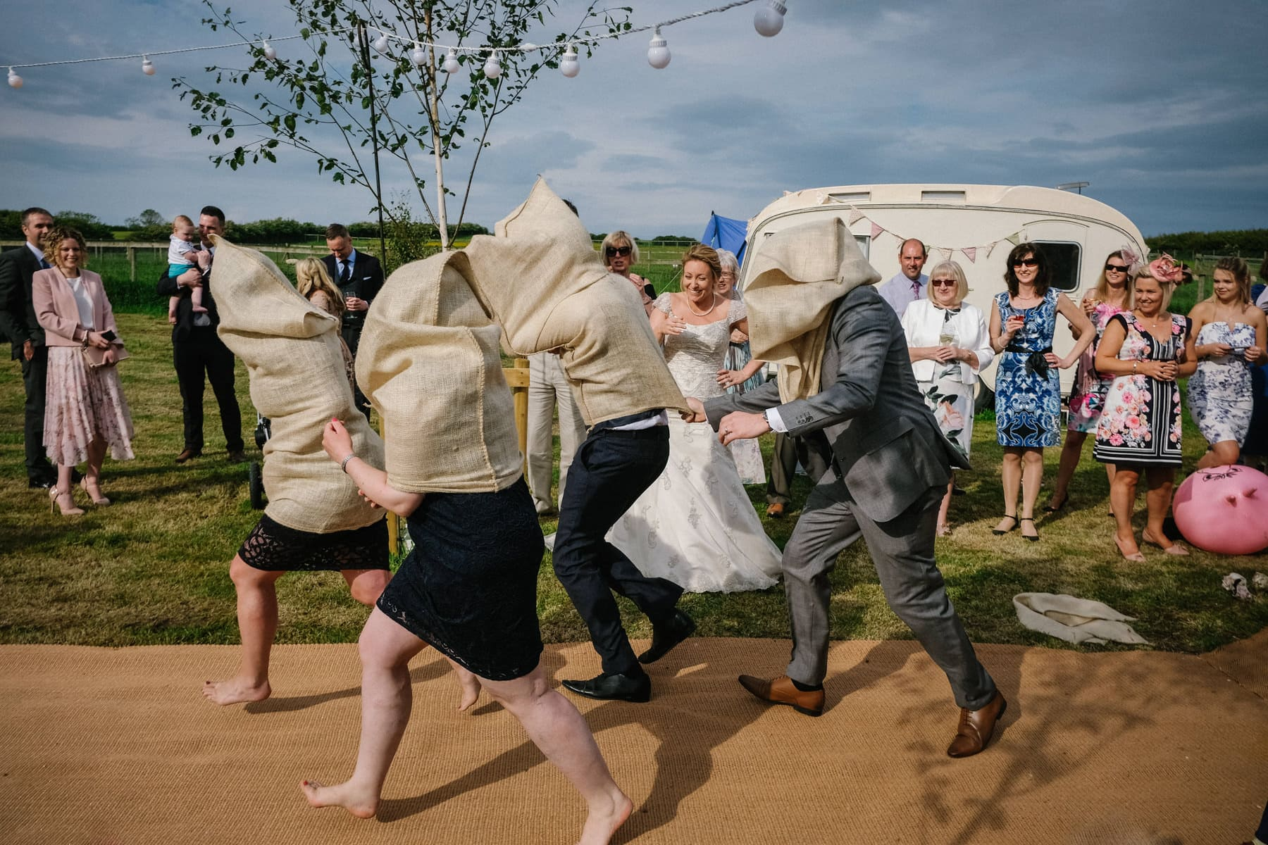 wedding guests racing outside with potato sacks on their heads