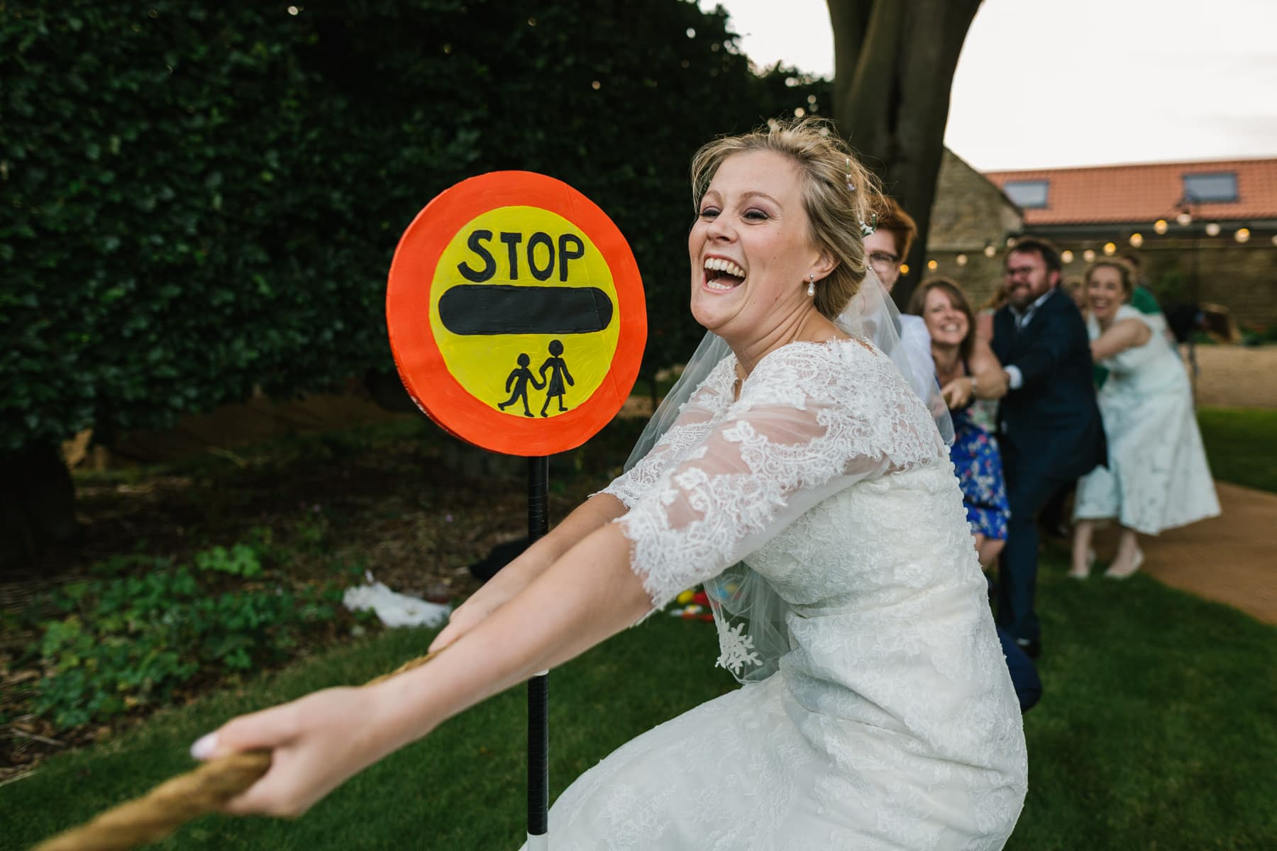 bride playing tug of war at her wedding