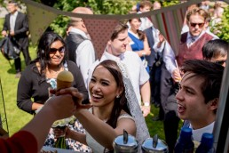 bride being given ice cream from the ice cream van at her summer wedding