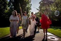 bridal party walking through Regents park with bubbles as part of their intimate London wedding celebrations