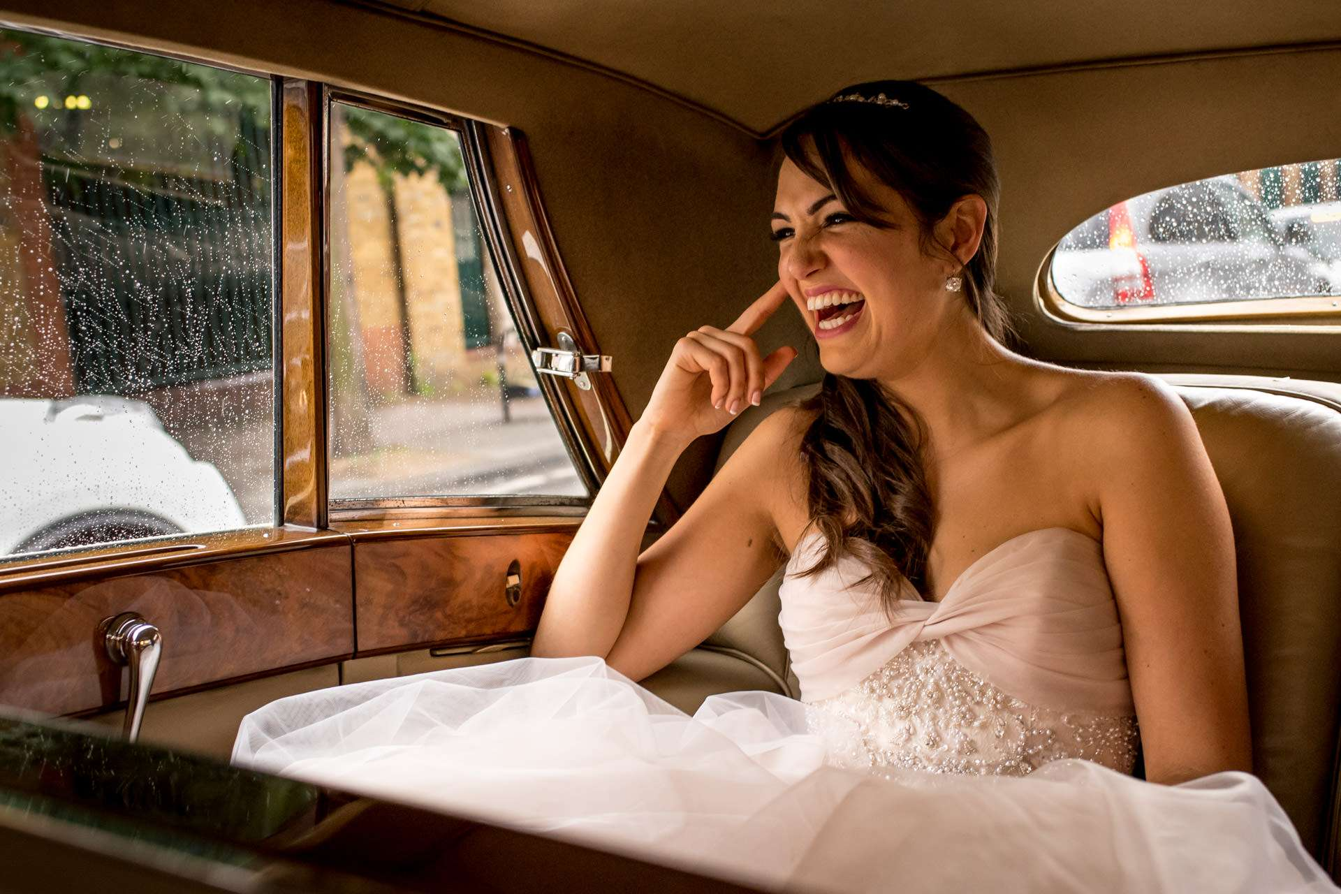 bride laughing in car on her way to landmark london wedding