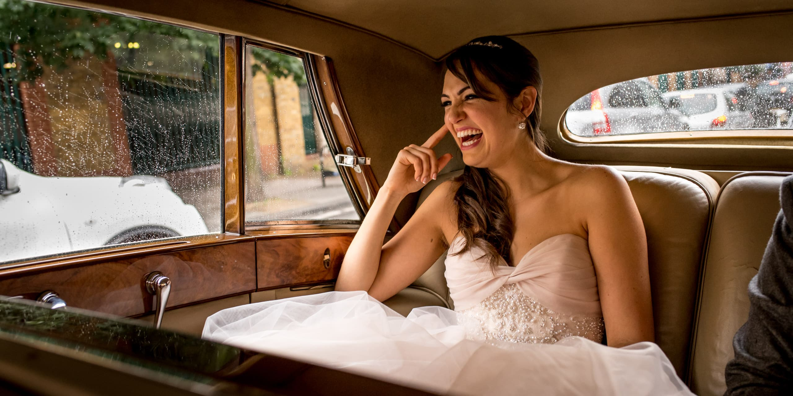 bride laughing in car on her way to landmark london wedding