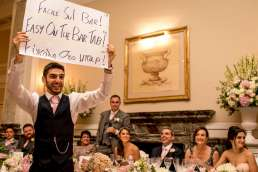 bestman holding up sign during speeches at a landmark london wedding