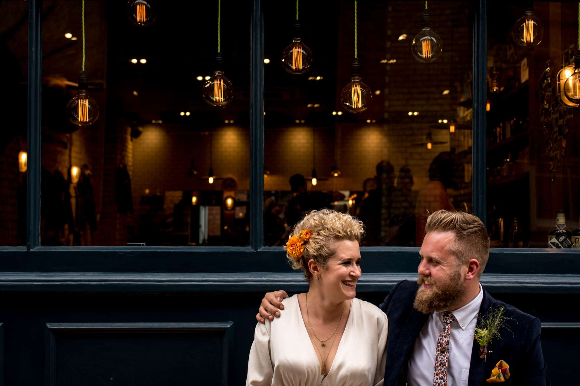 urban bride and groom sitting in from of shop taken by London wedding photographer
