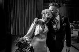 B&W photo of groom kissing bride at Stoke Newington Town Hall