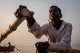 Boy rowing boat at sunrise on Ganges in Varanasi, India