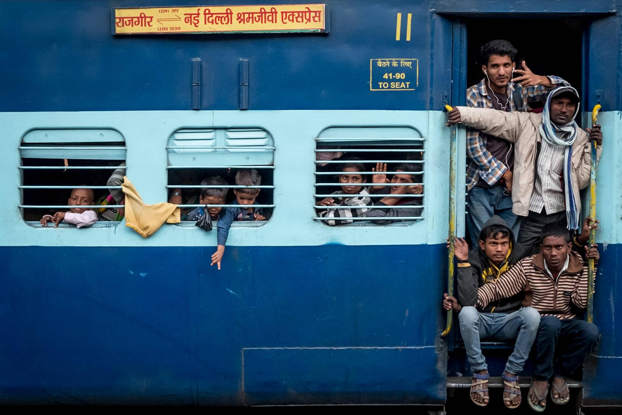 A blue train packed with people taken during india street photography trip