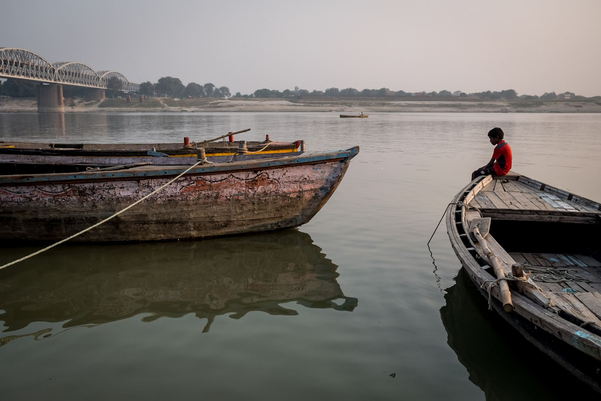 boy sitting on boat on the Ganges taken by Indian street photographer