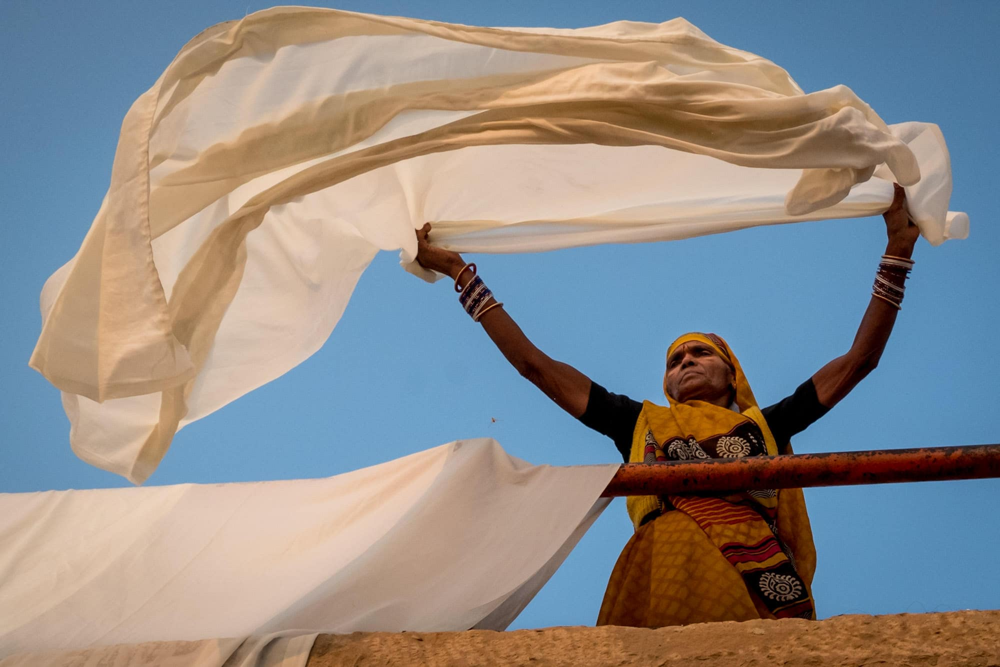 An Indian women trying sheets at sunrise in Varanasi