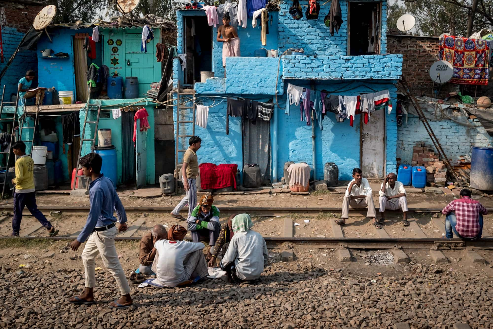 India street photography stories by the train tracks with colourful buildings