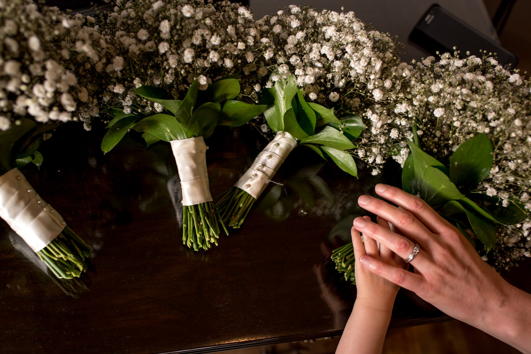 hands reaching for the wedding flowers