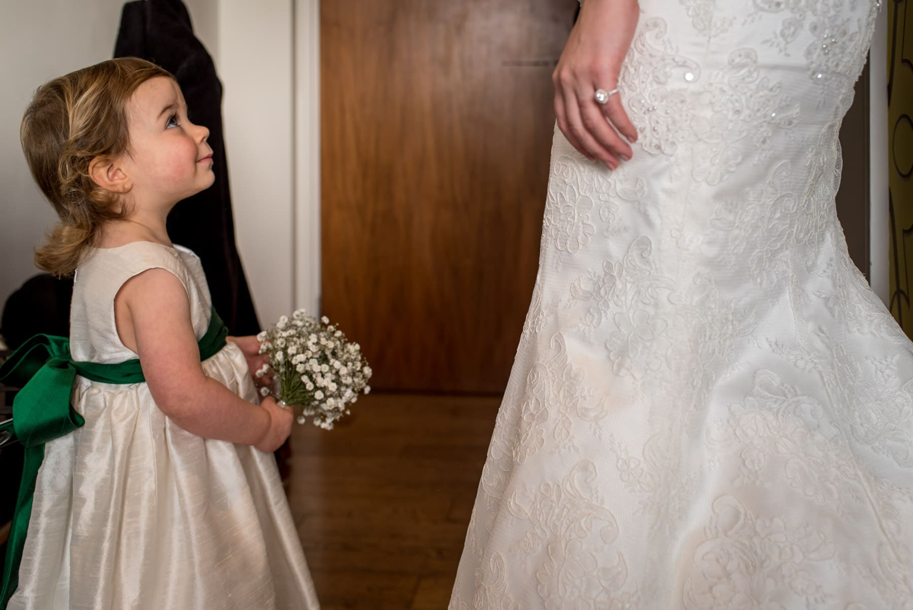 flower girl admiring the brides wedding dress