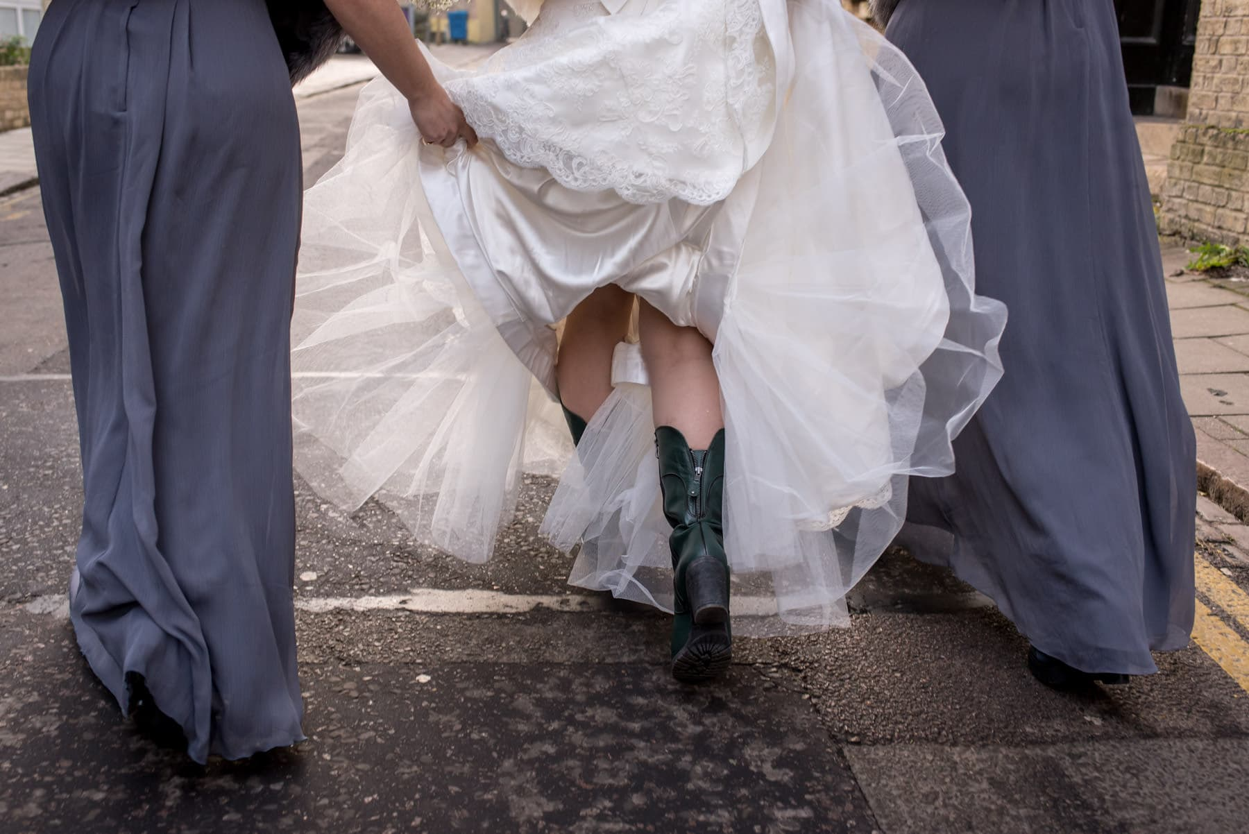 bride walking to her Cambridge wedding in green boots and her wedding dress