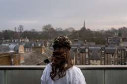 bride looking out at Cambridge on the morning of her wedding