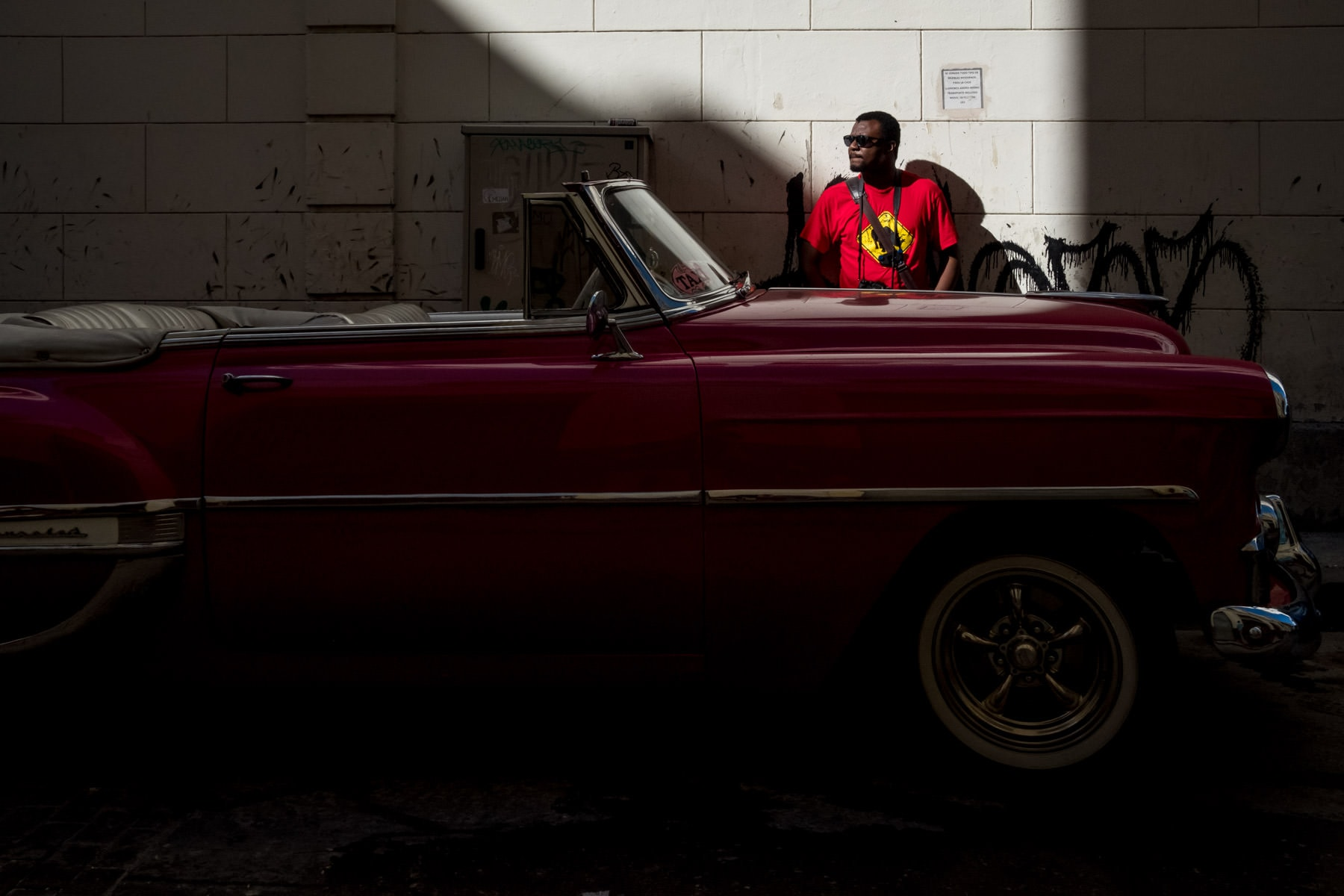 A street photographer standing in sun light in front of a pink Cuban car