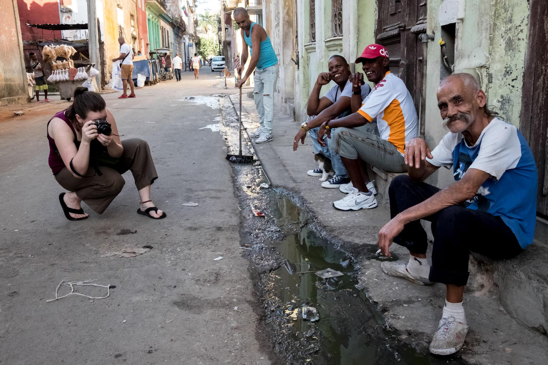 A street photographer photographing some men on the streets of Havana