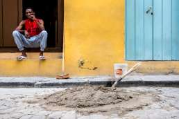 Cuban man in red t-shirt smoking a cigar in front of building site and yellow wall