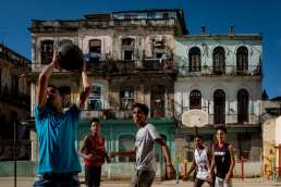 Photo of young Cuban men playing basket ball outside in the sun taken by Havana Street photographer Matt