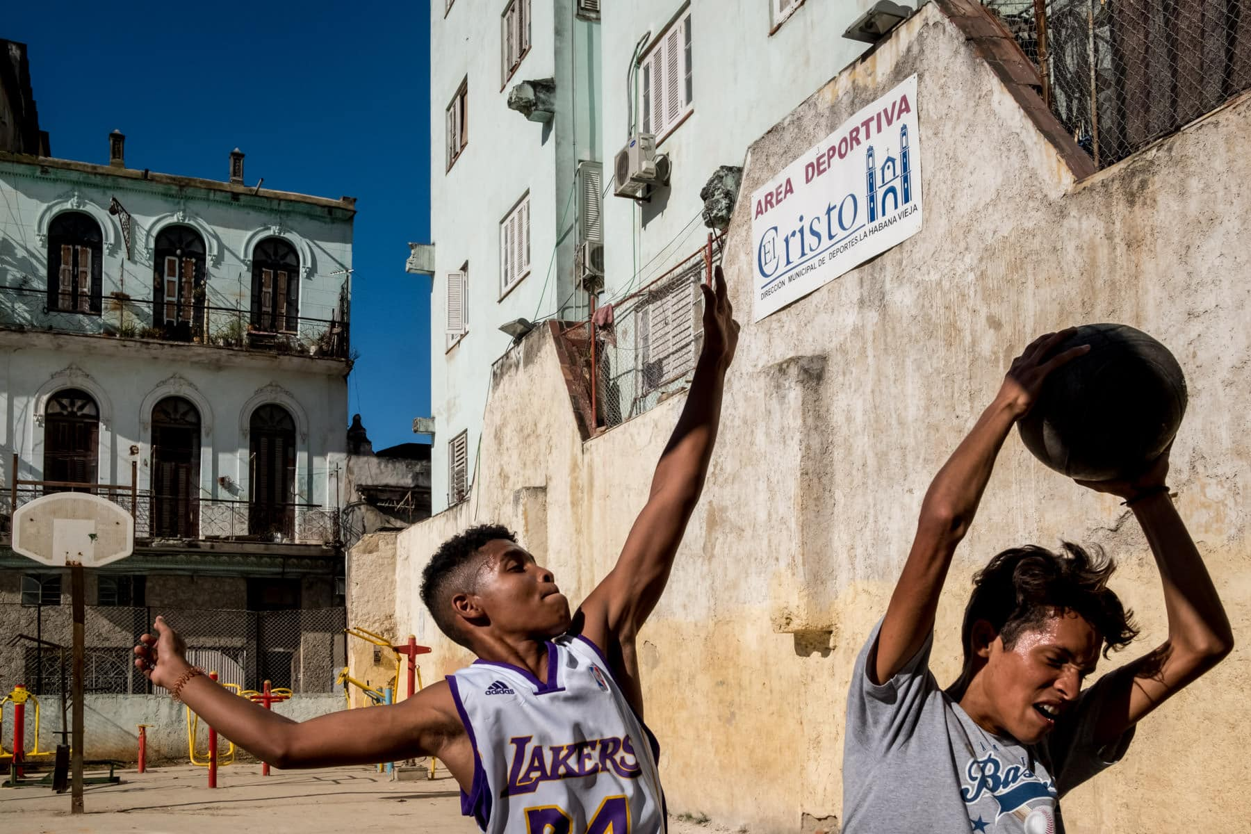 Young cuban men playing basket ball on the streets of Havana in the sun