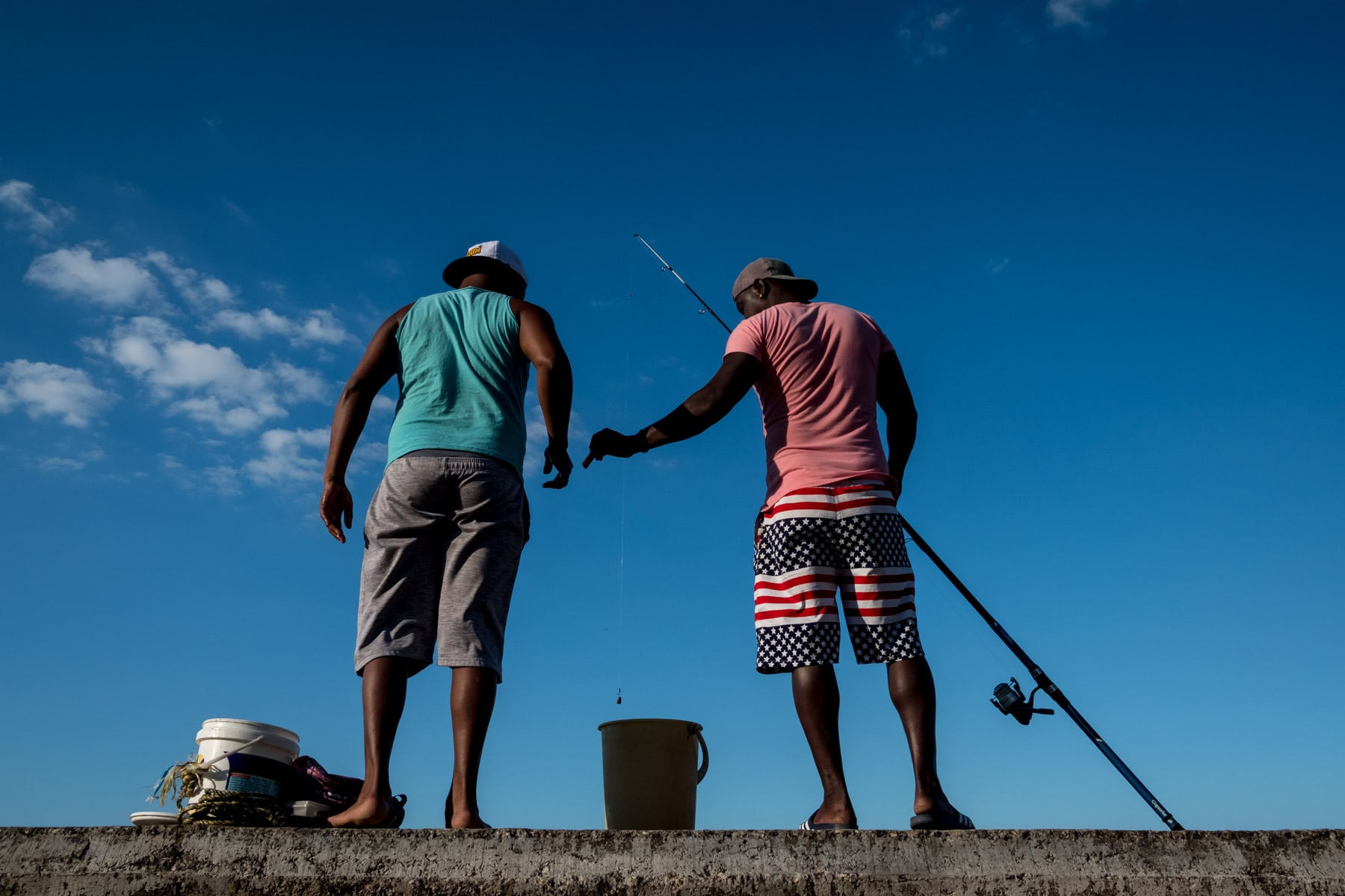 2 cuban fishermen standing on the Malecon in Havana with USA flag shorts
