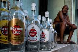 A Cuban man sitting on his porch with lots of empty bottles of Havana Club rum next to him on the streets of Havana