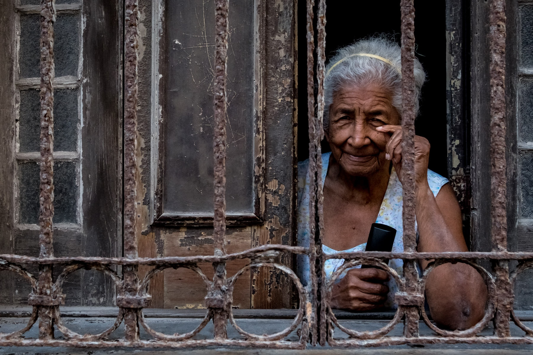 An old Cuban women looking through her window in Havana