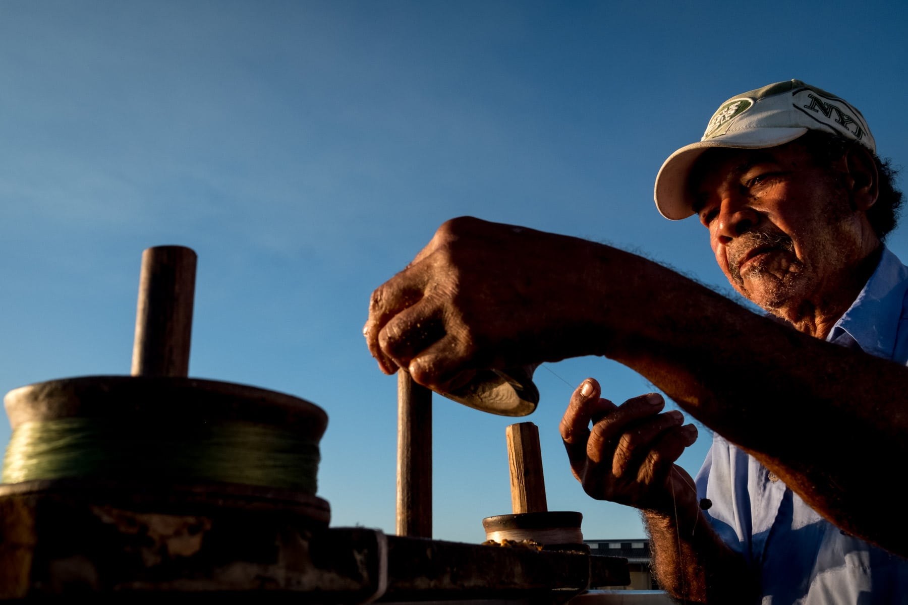 A Cuban fisherman at sunset casting lines against a blue sky taken by Havana street photographer Matt Badenoch