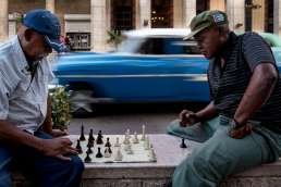 old men playing chess on the streets of Havana with blue Cuban car blurred in the background, taken by Havana street photographer Matt Badenoch
