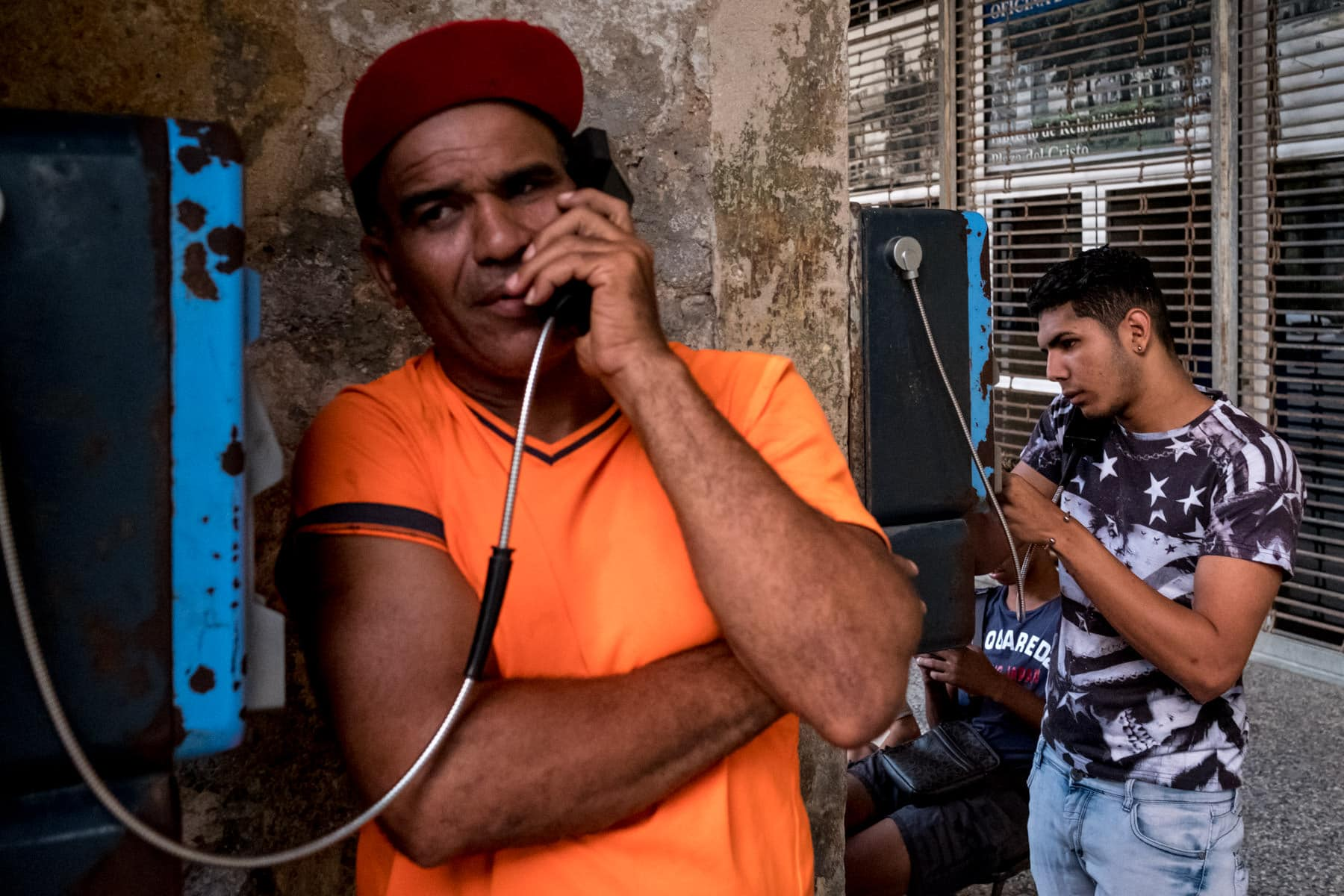 Cubans using telephone boxes in Havana, Cuba