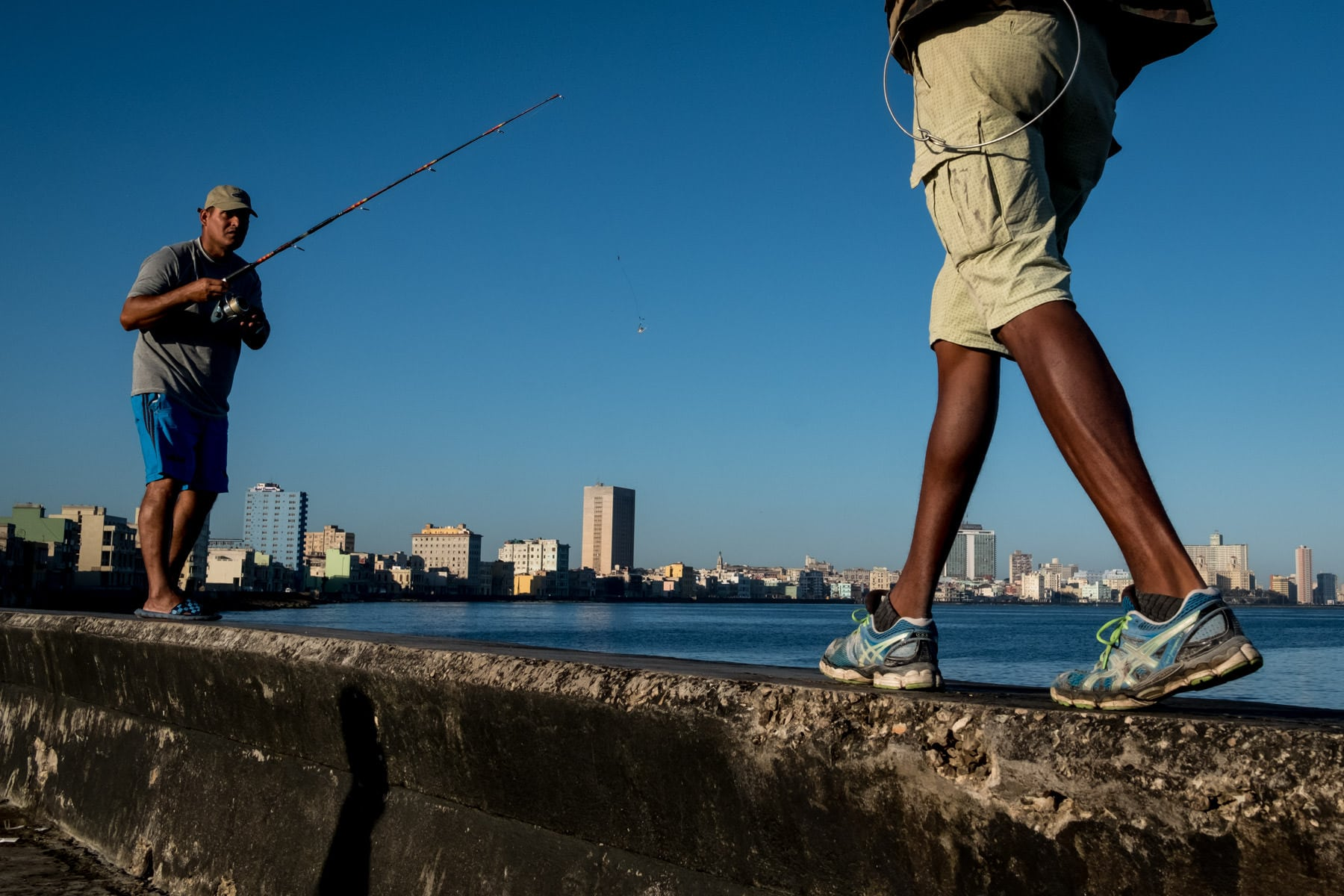 fishermen on the malecon with the Havana city sky line in the background