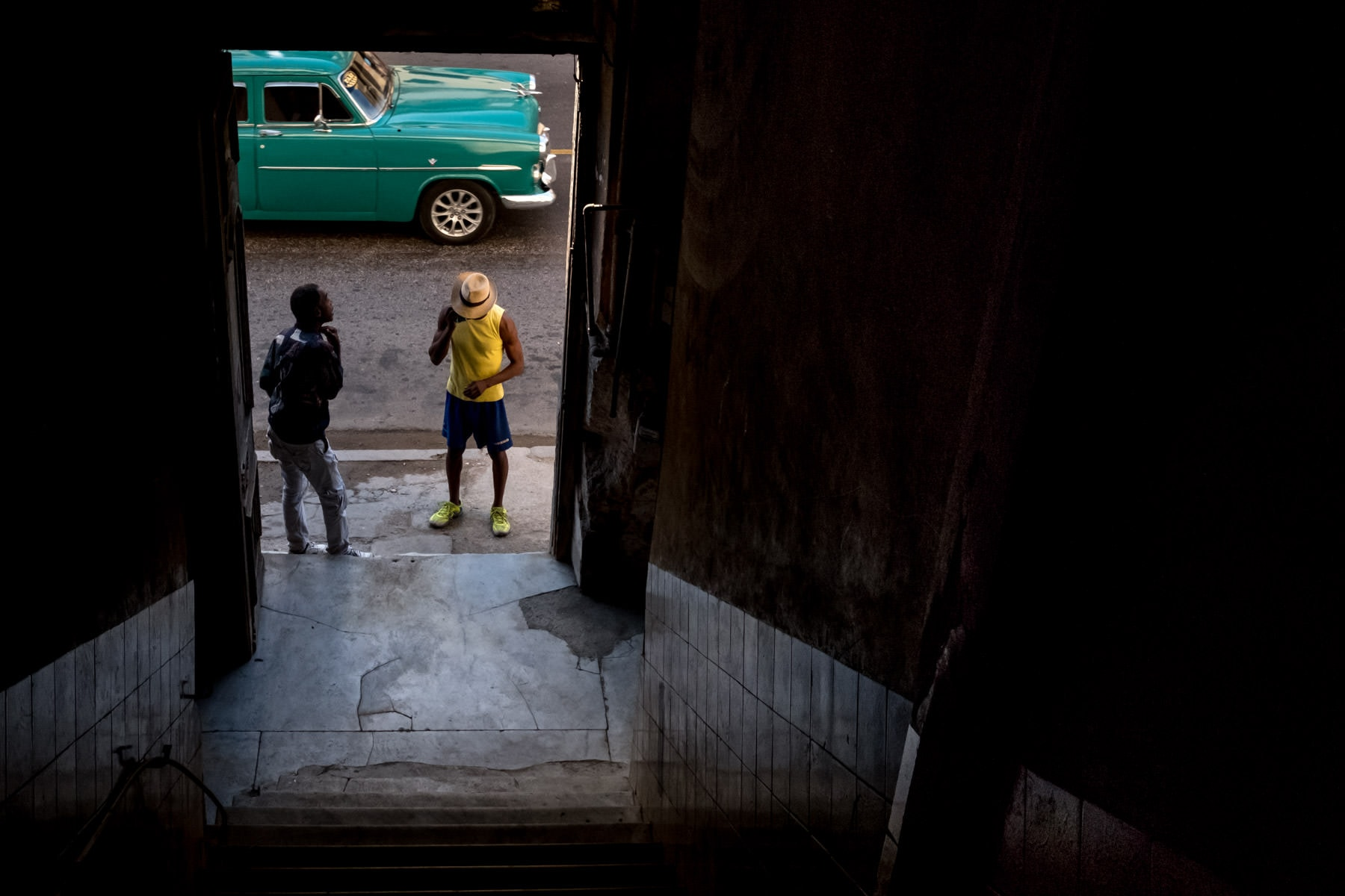 A green cuban car and man in yellow t shirt photographed through the door way of his casa in Havana, Cuba