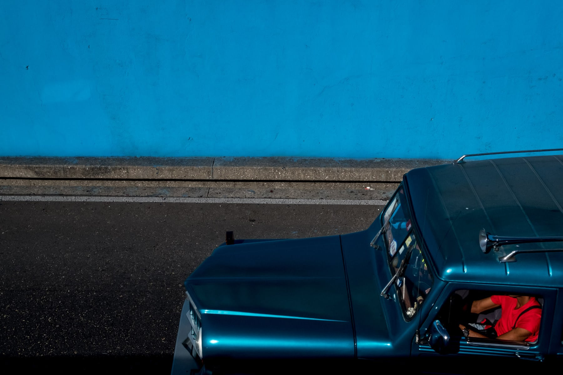 a blue car and man in red tshirt on the streets of Havana