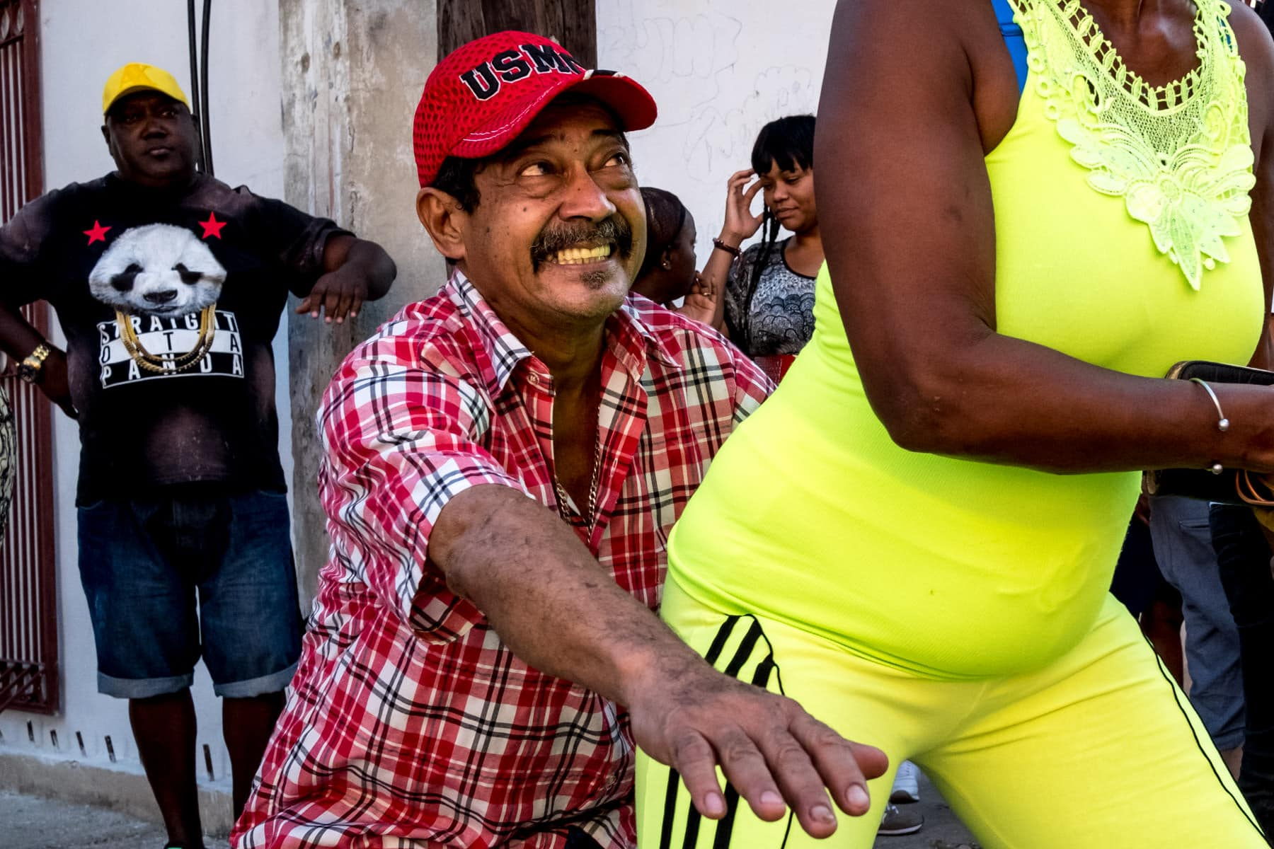 A Cuban man dancing with a women in a bright green/ yellow outfit on the steets of havana