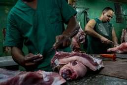 Butchers wearing green in a market in Havana