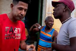 Men in bright t-shirts drinking coffee and smoking in Havana