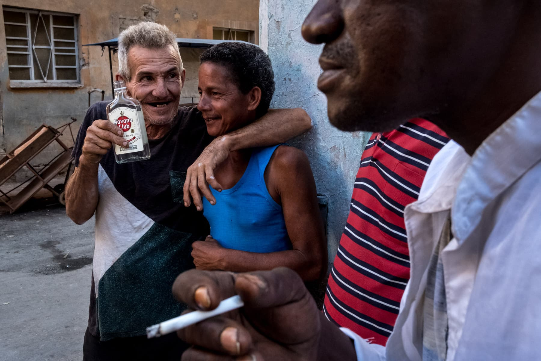 Old men drinking Havana Club rum and smoking on a street corner taken by Havana street photographer Matt Badenoch
