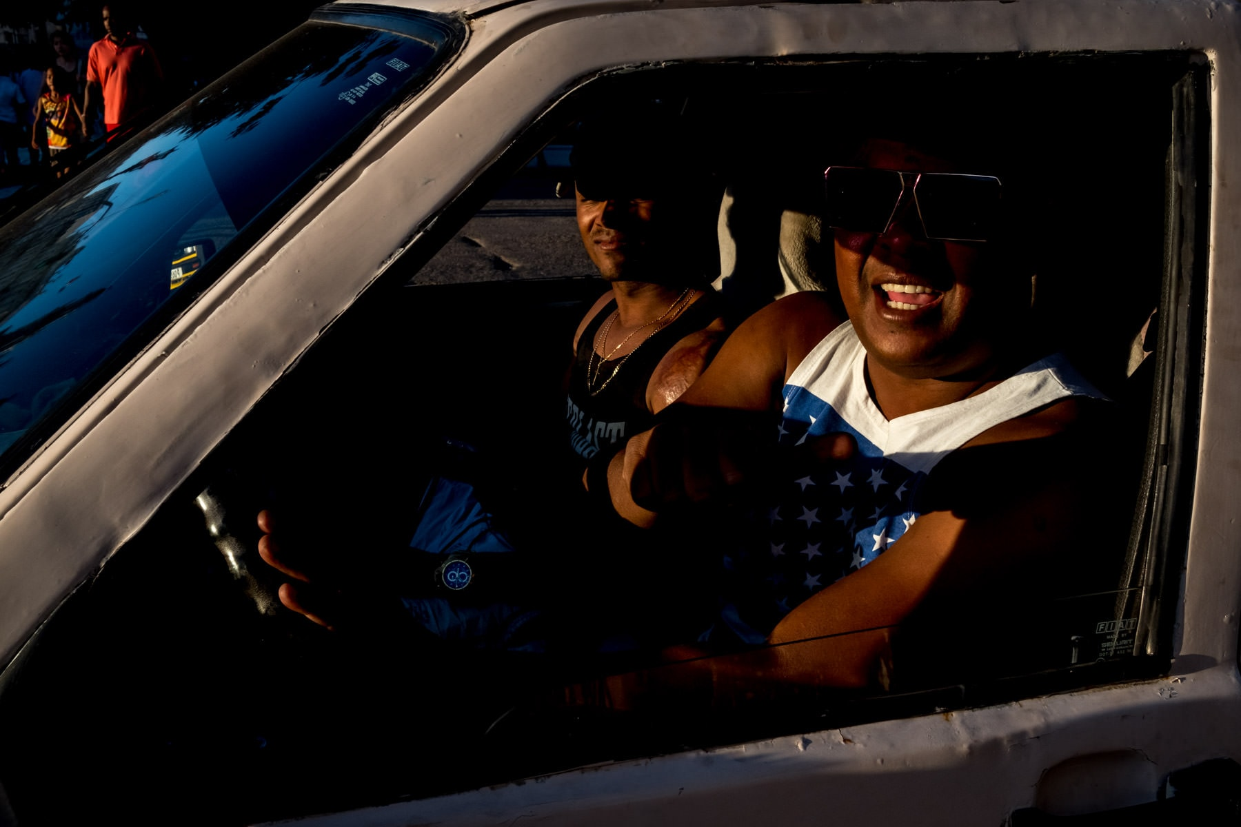 men in sunlight in a car wearing sunglasses in Havana, Cuba