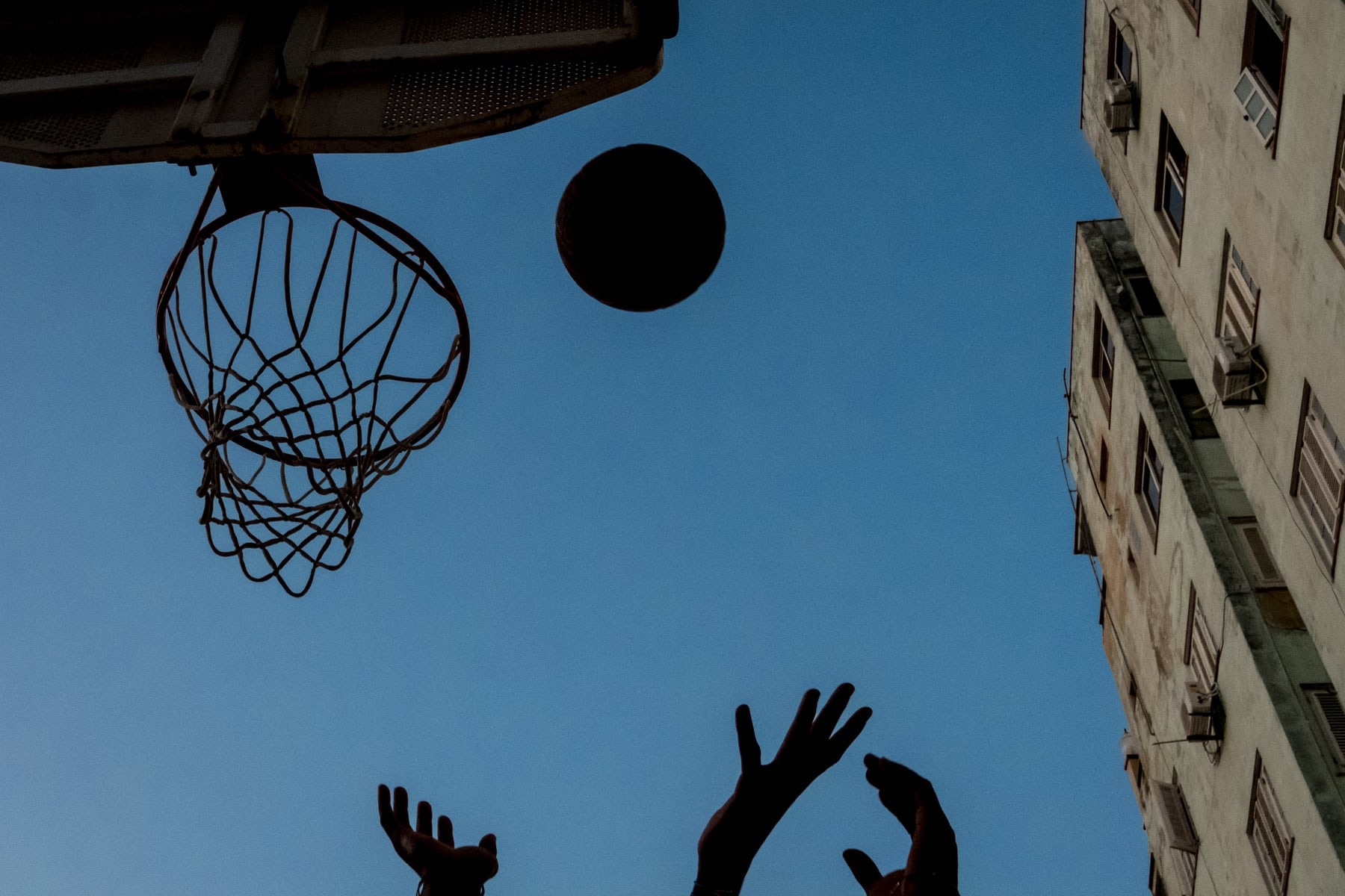 hands playing basket ball in havana, against a blue sky