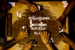 hands of old men playing dominos on the streets of Havana