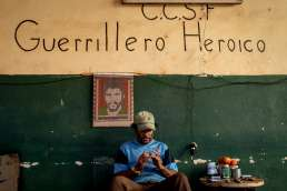 A cuban man in blue tshirt sits on a stool infront of poster of Che Guevara