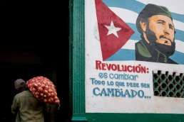 A man carrying a bag of potatoes next to a painting of Castro in Havana, Cuba
