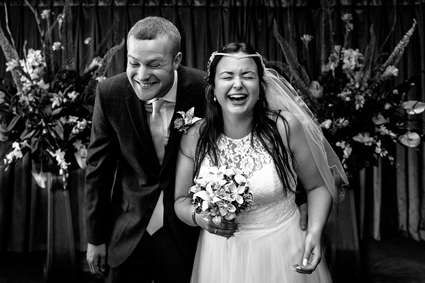 black and white photo of a bride and groom laughing hard at their cruise ship wedding