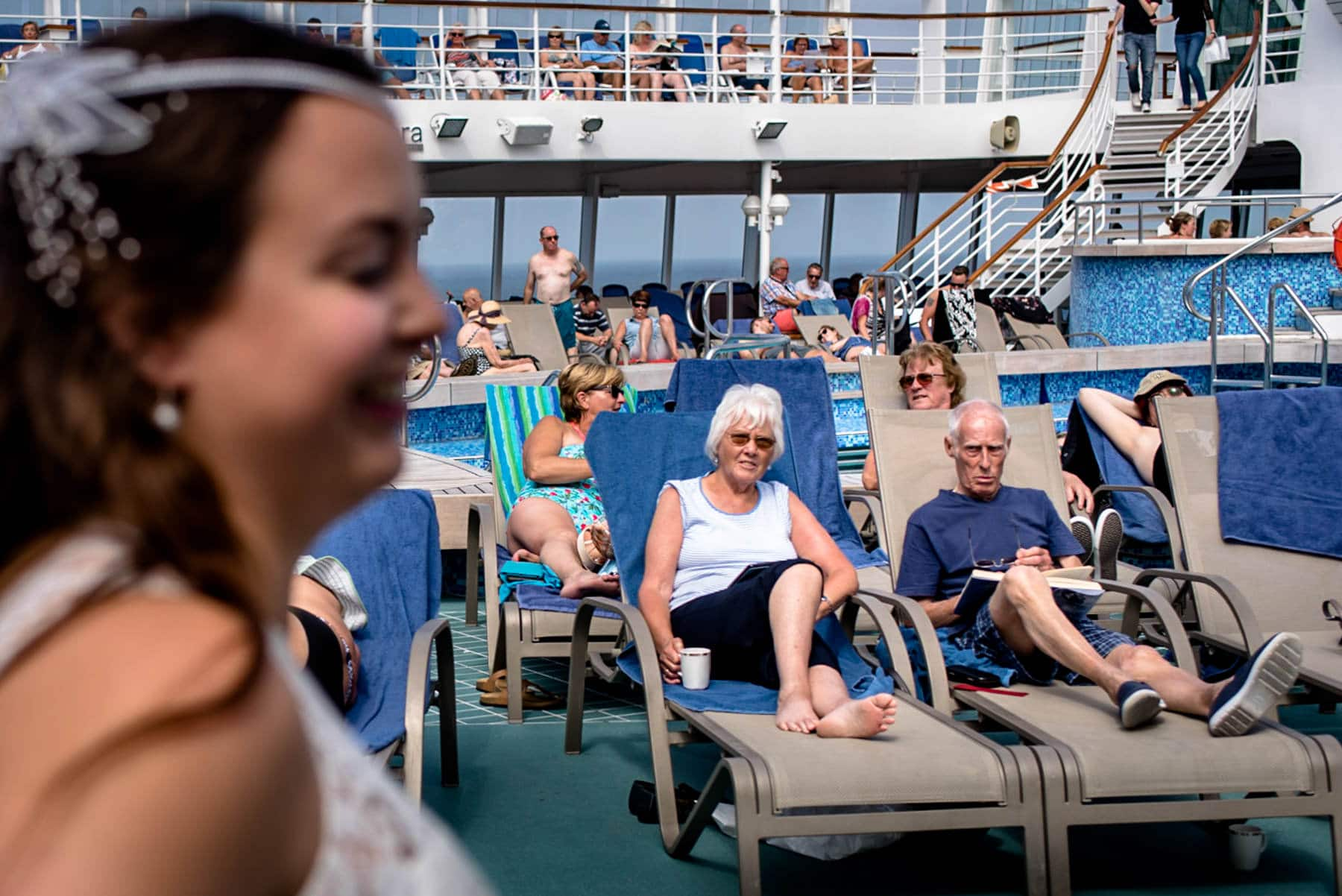 Cruise ship goers watch in confusion as a bride walks past