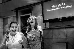 Bride in her wedding dress singing karaoke with one of her bridesmaids on a cruise ship