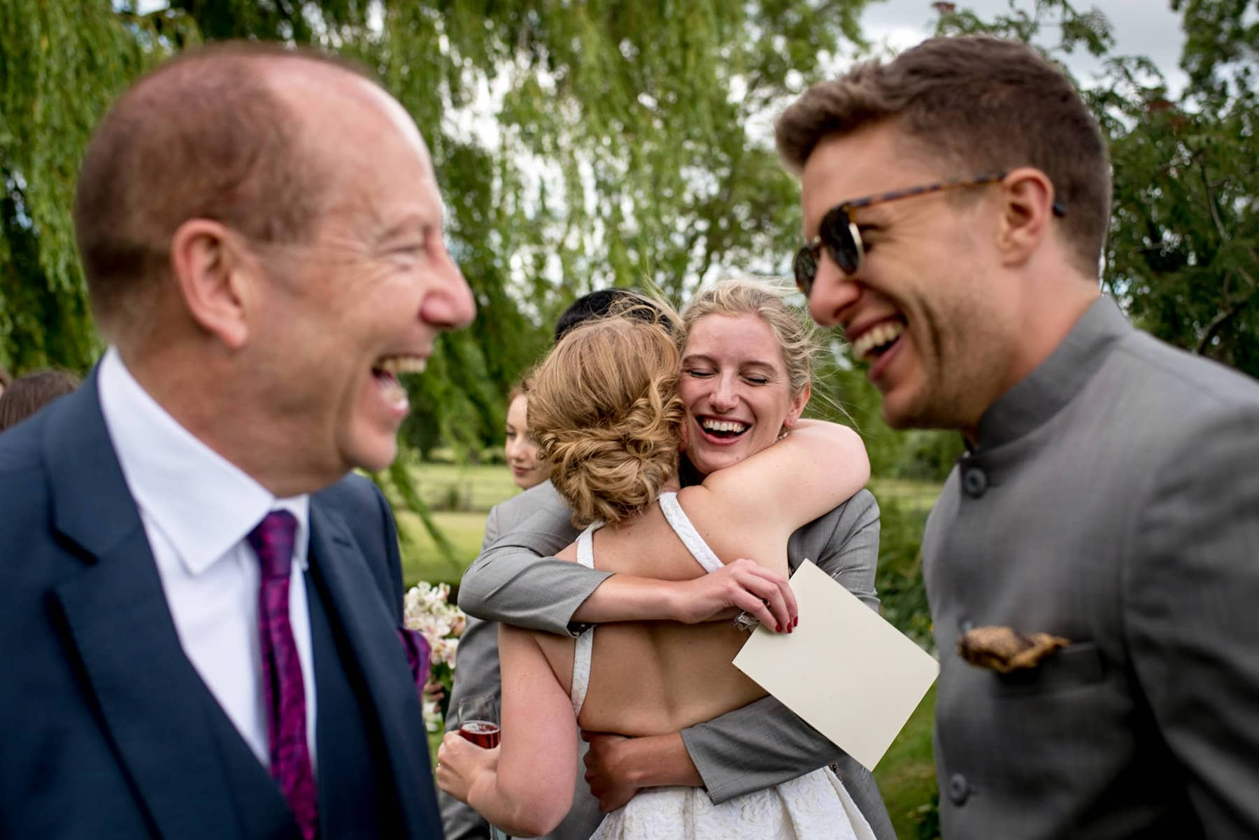 Wedding guests laughing and hugging each other at a garden party wedding in Oxfordshire